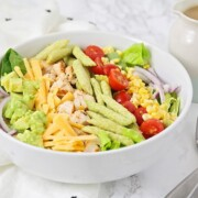 grilled chicken salad with lettuce, cheese, corn, tomatoes, and snap peas in a white bowl