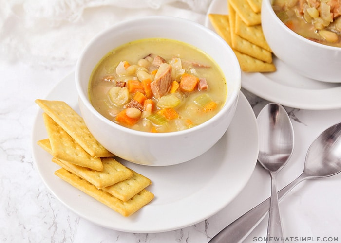 A bowl of soup filled with ham, white beans and vegetables