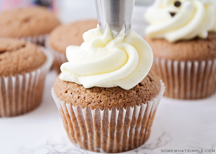 white frosting being piped onto a cupcake