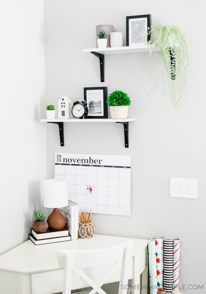 shelves with decorations on a wall with a small corner desk below them