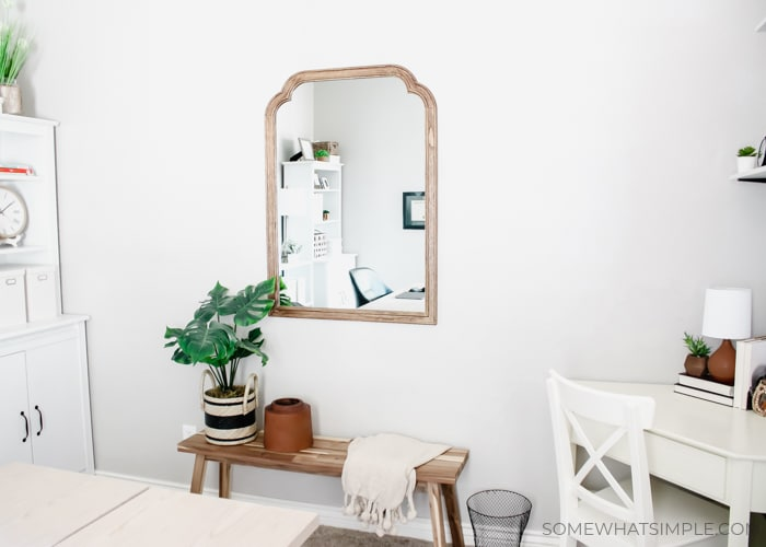 a mirror on a wall next to a white corner desk