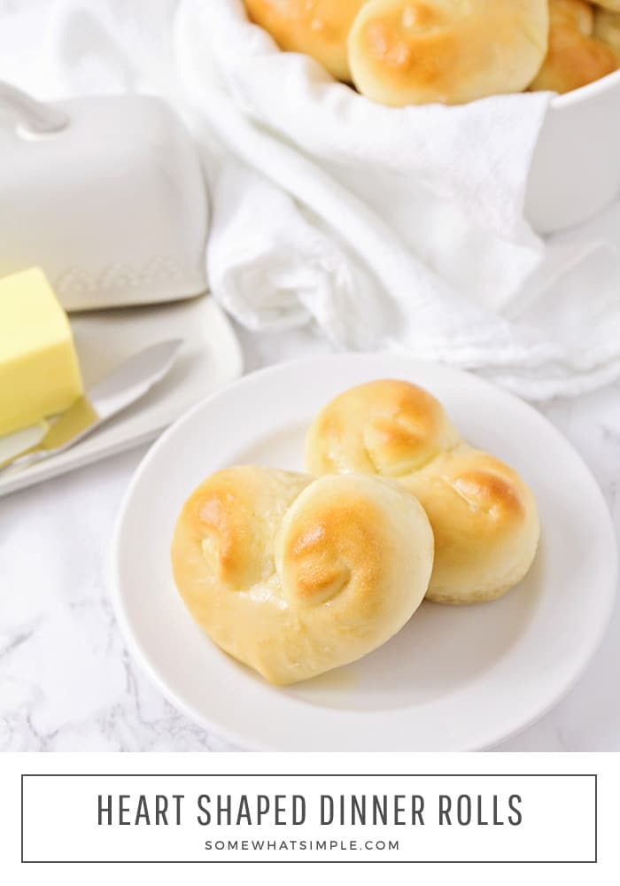 These heart shaped dinner rolls are a fun addition to any romantic homemade dinner.  It just a few simple steps you can transform what would be an ordinary dinner roll into a heart shaped masterpiece.  Whether it's Valentine's Day your anniversary or any other special occasion, this bread is perfect for that special dinner. #heartshapedbread #heartshapeddinnerrolls #heartshapedrolls #easyheartshapeddinnerrolls #howtomakeheartshapeddinnerrolls via @somewhatsimple