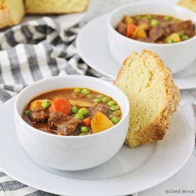 two bowls of Irish stew with a side of soda bread