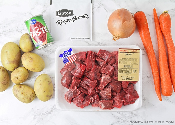 potatoes, an onion, carrots, chopped beef and tomato paste on a counter