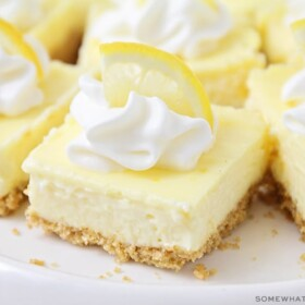 lemon cheesecake squares topped with whipped cream