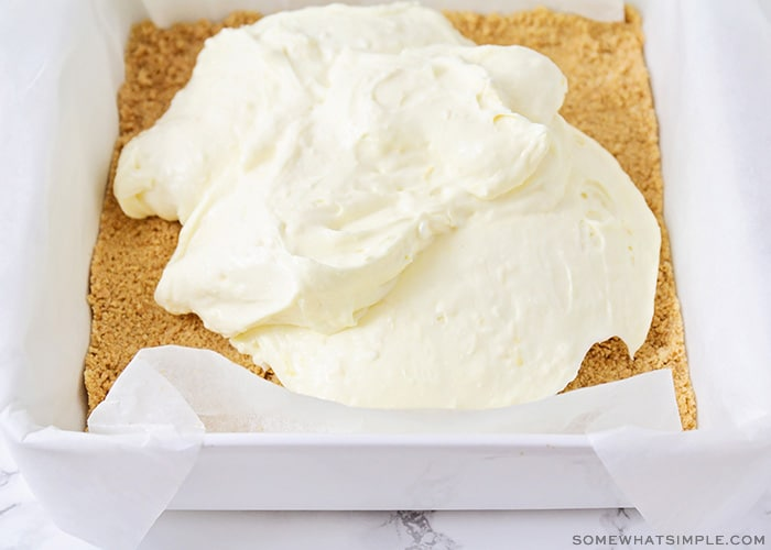 a cream cheese mixture poured on top of a graham cracker crust