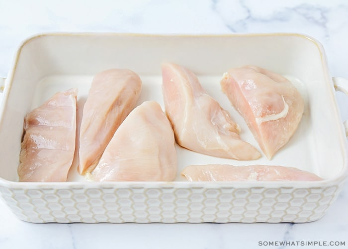 a baking dish filled with raw chicken breasts