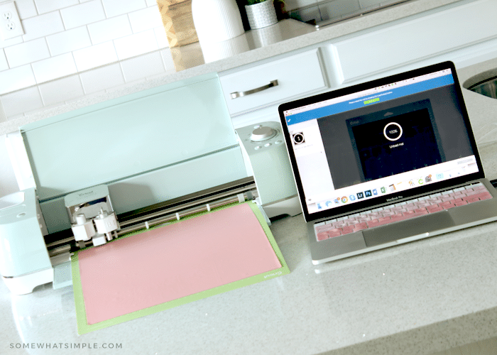 a cricut machine next to a laptop