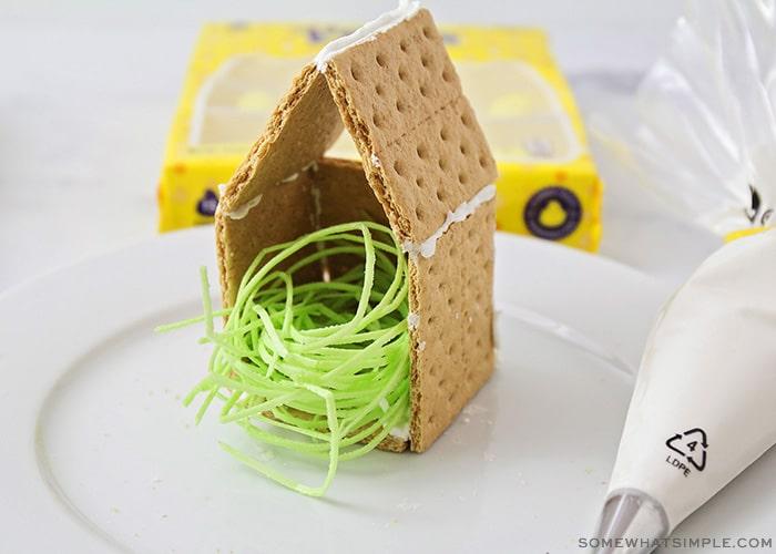 a graham cracker birdhouse with edible green grass