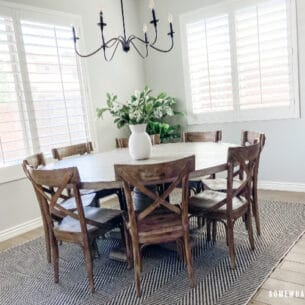 Dining room with round table on rug with simple centerpiece