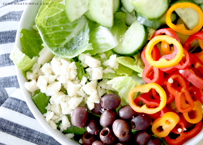 a salad with olives, peppers, cucumbers, cheese, and romaine lettuce