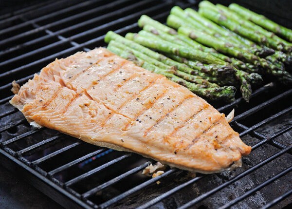 grilled salmon on the grill next to asparagus stalks
