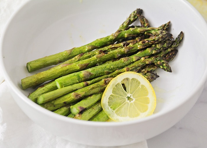 stalks of grilled asparagus in a white bowl next to a lemon slice