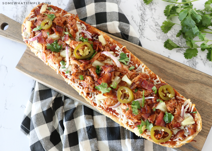 a loaf on a cutting board of BBQ Chicken French Bread Pizza