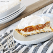 A slice of Pumpkin Pie Cheesecake on a white plate