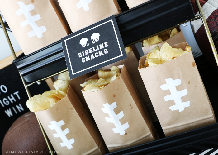 brown paper bags with white tape in the design of football laces filled with chips