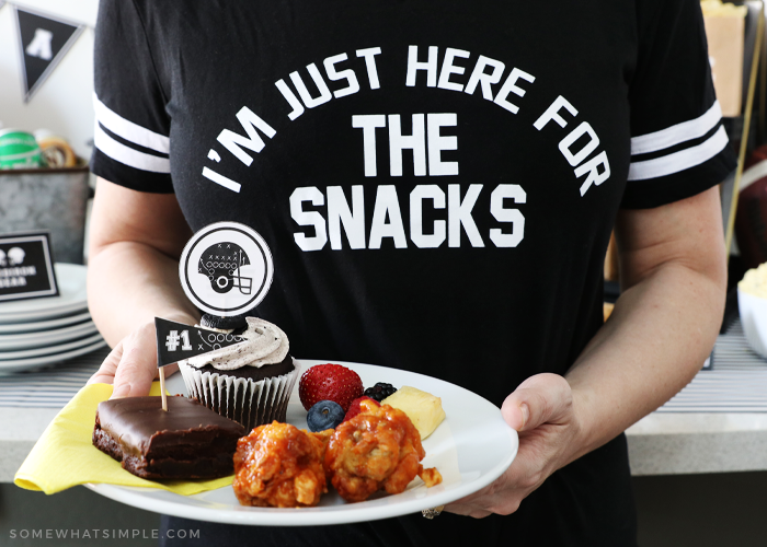 woman wearing black shirt holding a plate of party foods