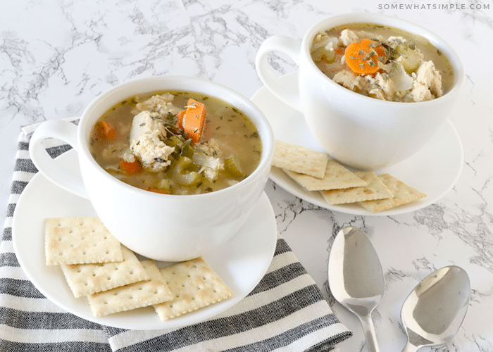 cups of chicken and rice soup with crackers on a counter