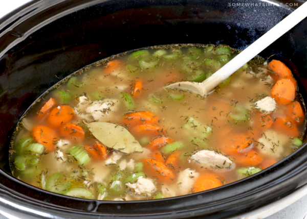 stirring the ingredients of a chicken and rice soup in the crockpot