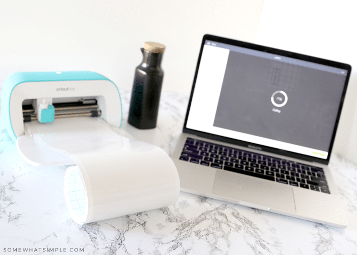 laptop and cricut supplies on a counter