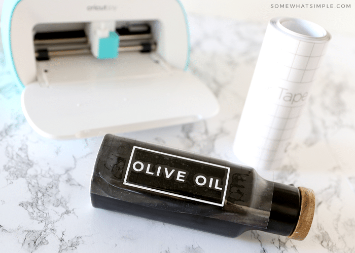 olive oil bottle on the counter with a cricut machine in the back