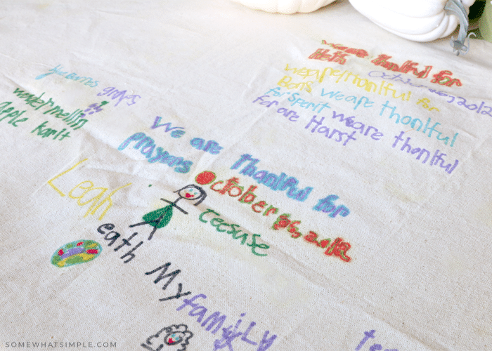 6 year old marker drawings of things she is thankful for on a thanksgiving tablecloth