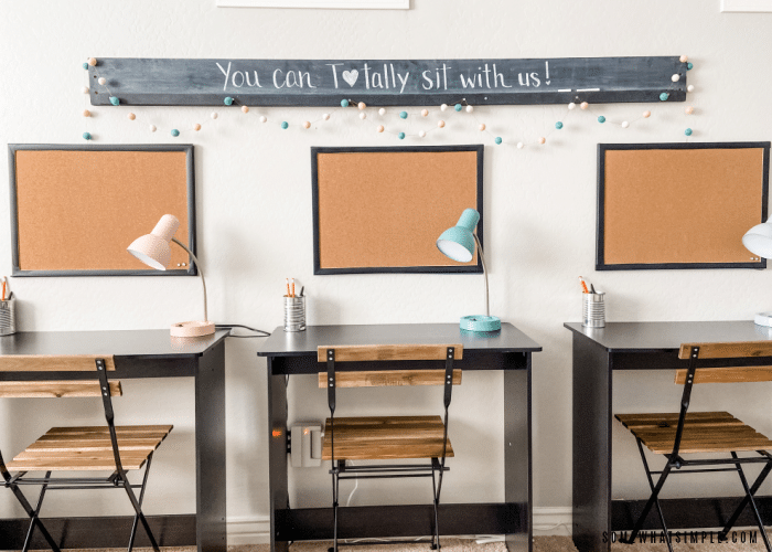 desks against the wall with corkboards and a chalkboard