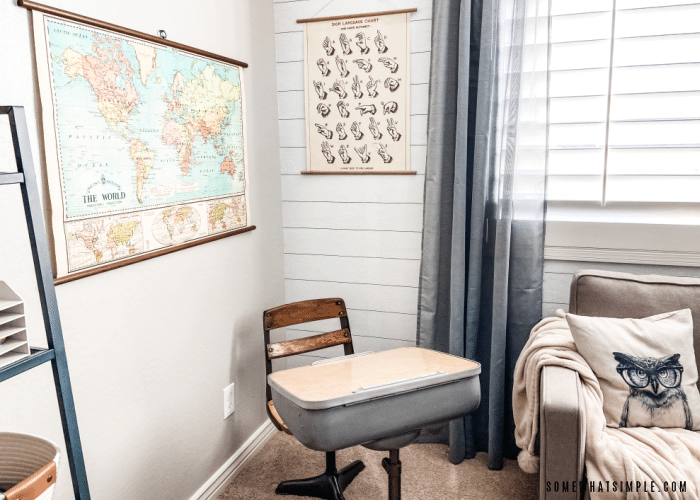 vintage desk in the corner of a room with a sign language and world map poster