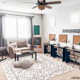 neutral homeschool room with desks, a couch and rug