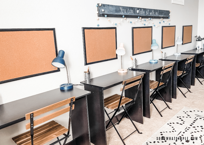row of desks with cork boards above each one