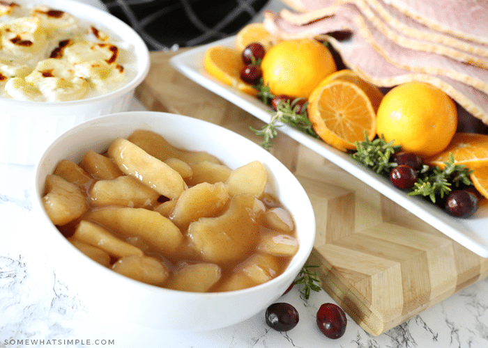 cinnamon apples in a bowl surrounded by food for the holidays