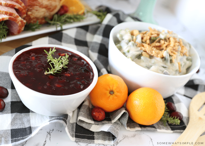 cranberry sauce, fresh oranges, and green bean casserole sitting on a counter