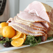 an Instant Pot Ham on a white tray with a basket of rolls in the background