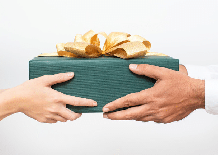 woman handing man a gift box wrapped in green paper and a gold bow