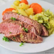 corned beef and cabbage plated on a white plate with steamed veggies on the side