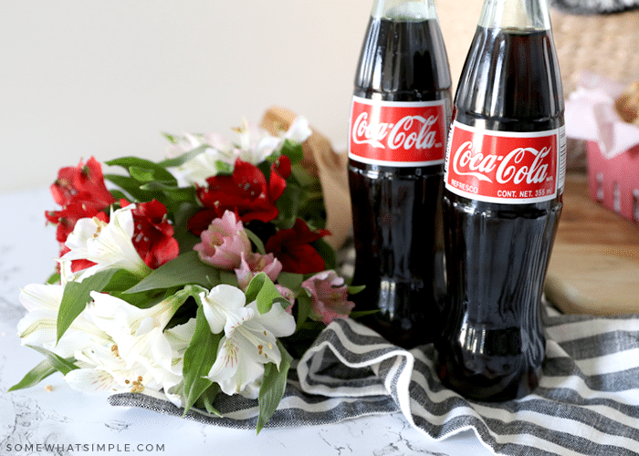 bouquet of flowers next to two bottles of coke
