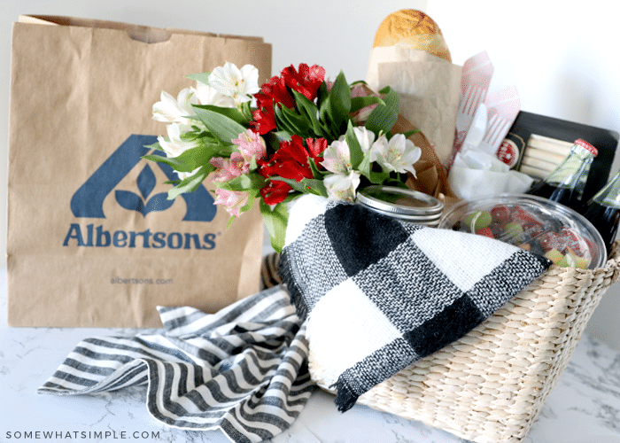 picnic basket filled with food and a blanket next to a brown grocery bag