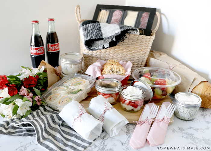 an array of food laid out with a picnic basket for a picnic date