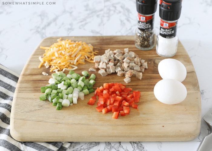 eggs, cheese, sausage, green onions, red bell peppers, salt and pepper on a cutting board