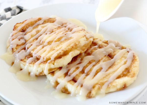 drizzling glaze over cinnamon roll pancakes