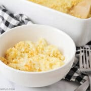 white bowl with a serving of cheesy potato casserole with casserole pan in background