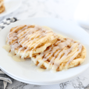 Cinnamon Roll Pancakes on a white plate with striped napkin