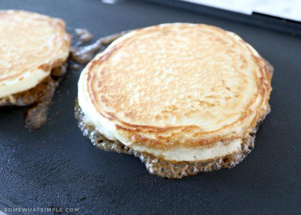 golden pancakes on a black griddle