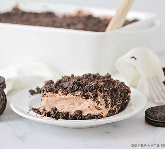 slice of chocolate cake with crushed oreos on top and the full cake in the background