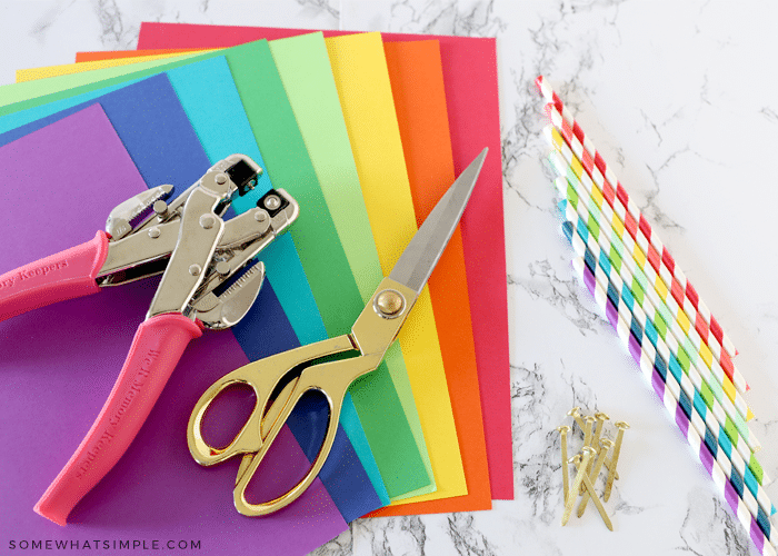 colorful paper, paper straws, scissors, hole punch, brads