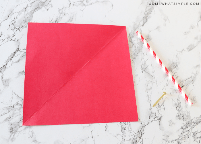 piece of red paper on the counter with a straw next to it