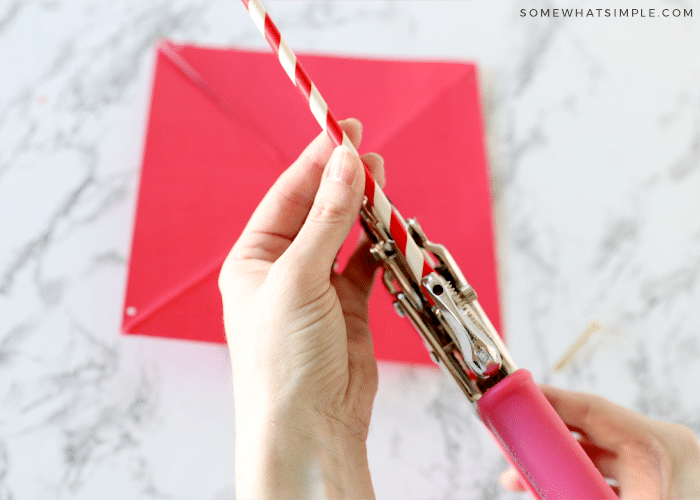 using a hole punch to put a hole in a paper straw