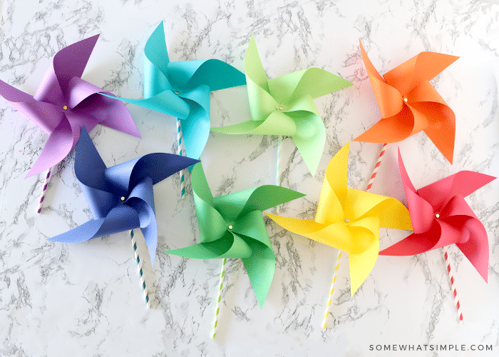 8 paper pinwheels in different colors of the rainbow laying on the counter