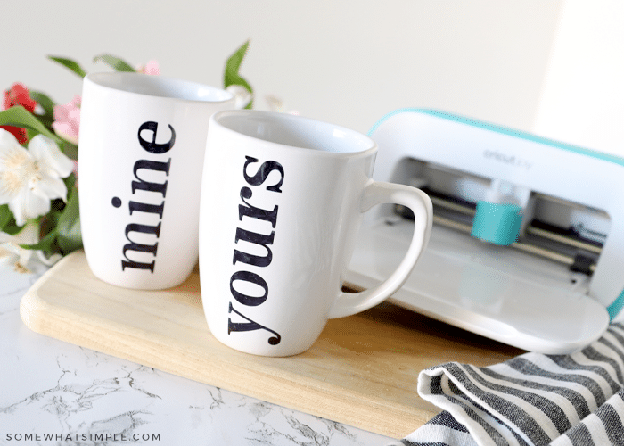 two white mugs colored with a sharpie. a cricut cutting machine in the background