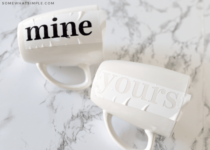 """two white mugs on the counter, one with black letters that spell out """"mine"""" and the other with a whit stencil attached to it that says """"yours"""""""